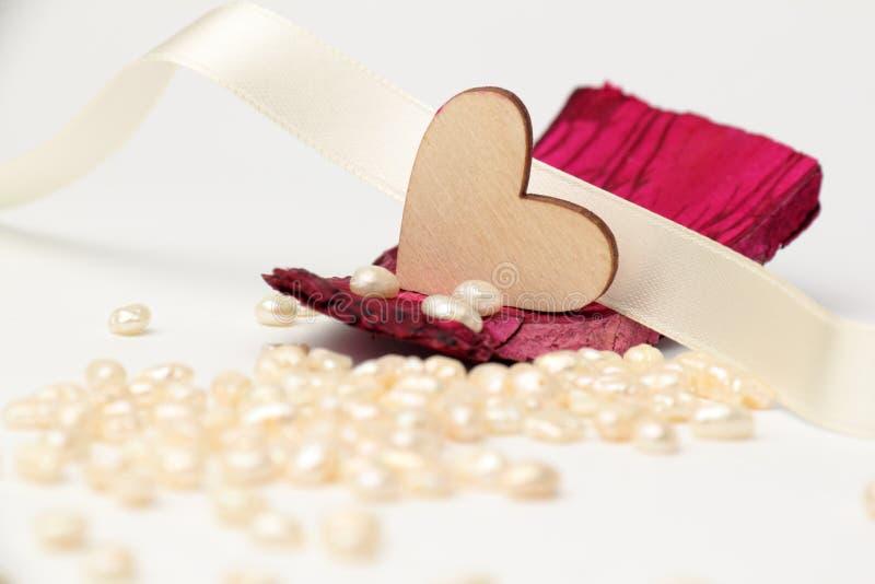 Corazón de madera en caoba de la madera de deriva con las perlas en el fondo fotografía de archivo