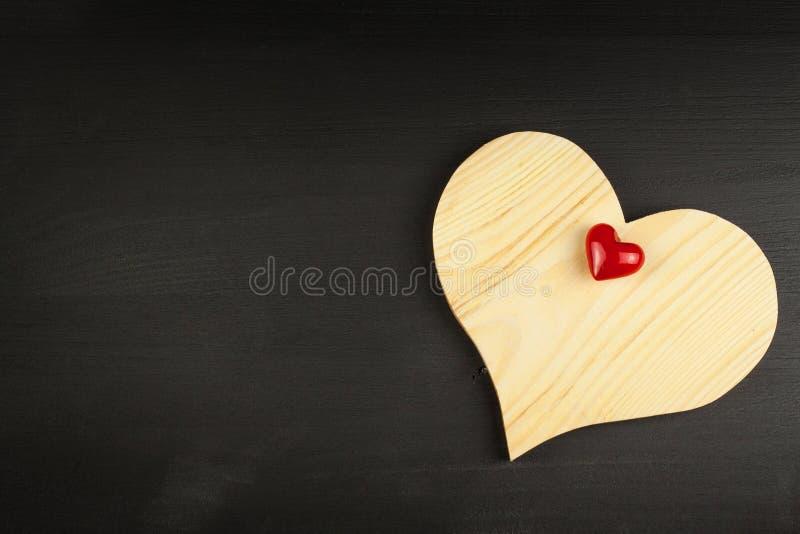 Corazón de madera en fondo negro Deseo para el día del ` s de la tarjeta del día de San Valentín del St Lugar para el texto imagen de archivo