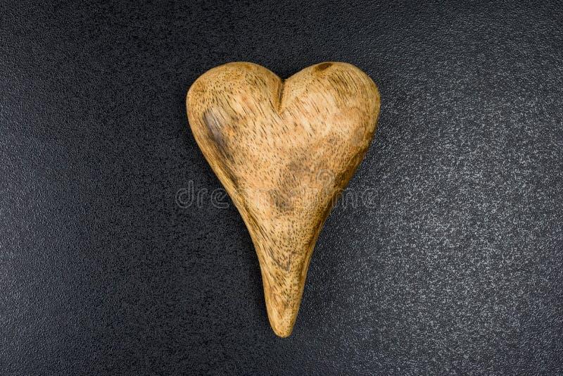 Corazón de madera en un fondo áspero negro, aislado en fondo negro con la trayectoria de recortes y espacio de la copia en el izq imagenes de archivo