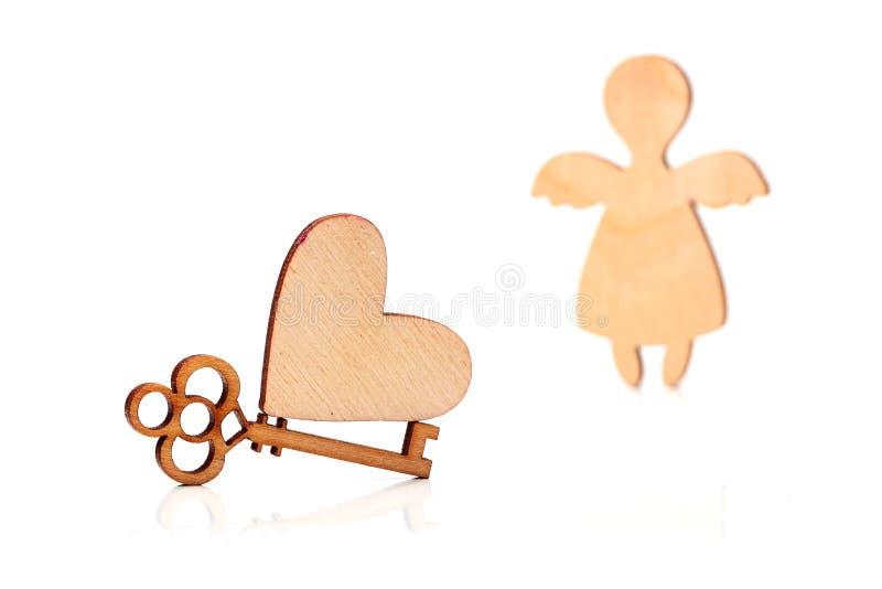 Corazón de madera, llave y un ángel imágenes de archivo libres de regalías