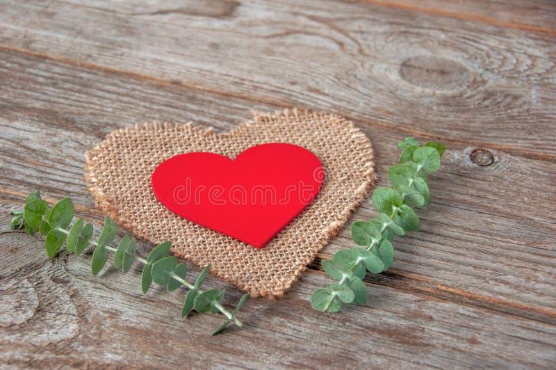Corazón de madera rojo decorativo encendido en una servilleta de la arpillera en la forma o foto de archivo