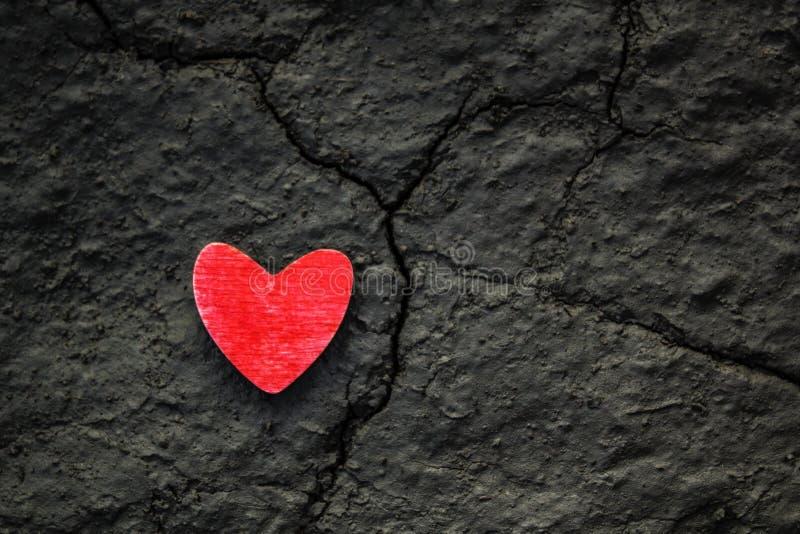 Corazón de madera rojo en una tierra gris seca agrietada Roto encima de corazón, concepto de la vida imagenes de archivo