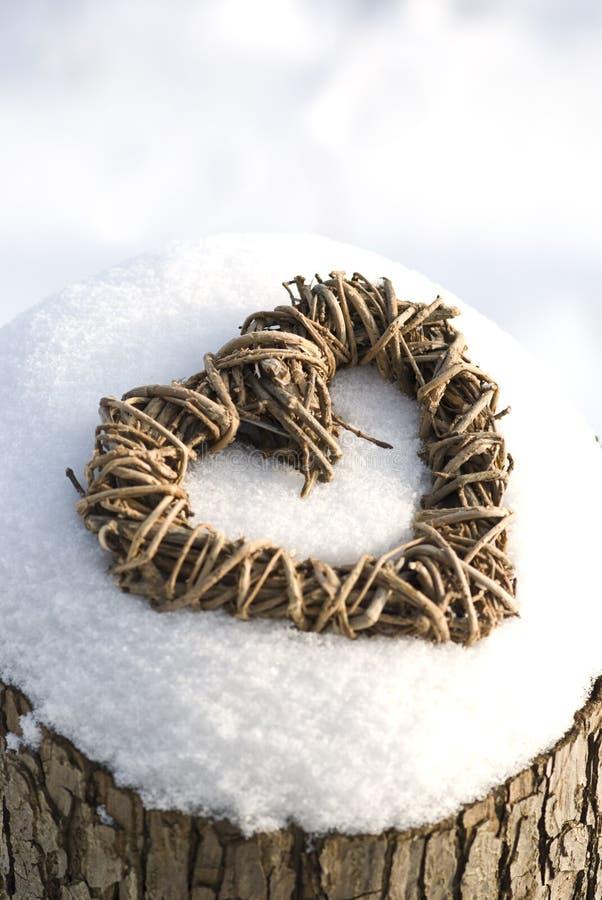 Corazón de mimbre en nieve fotografía de archivo