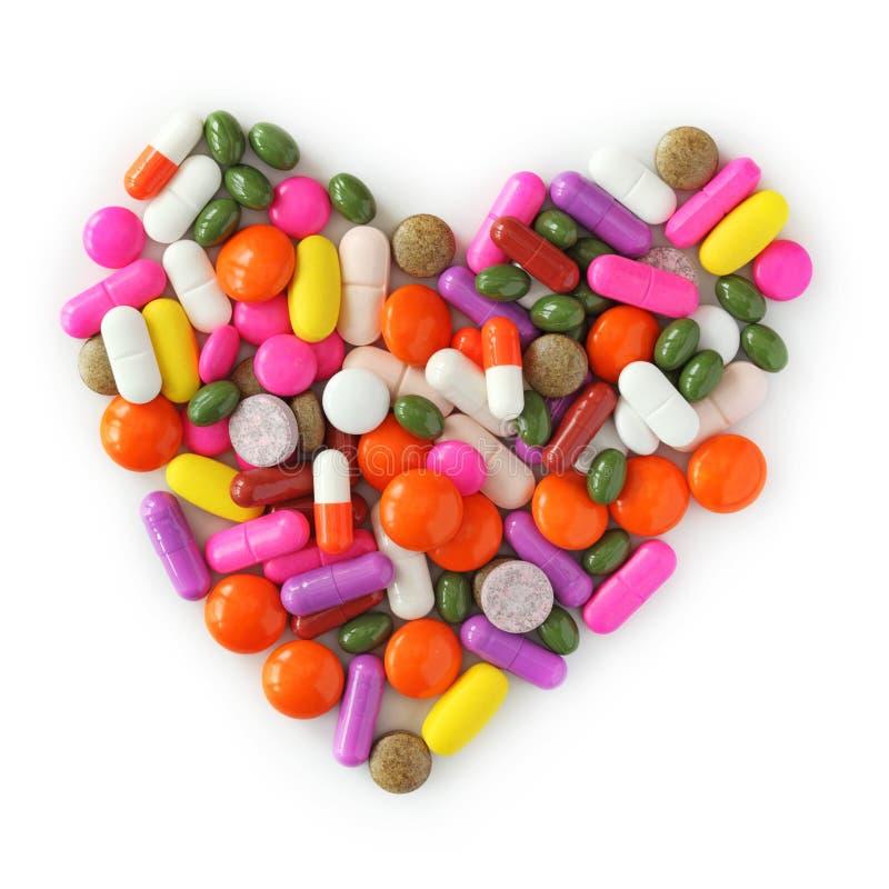 Corazón de píldoras y de cápsulas fotos de archivo