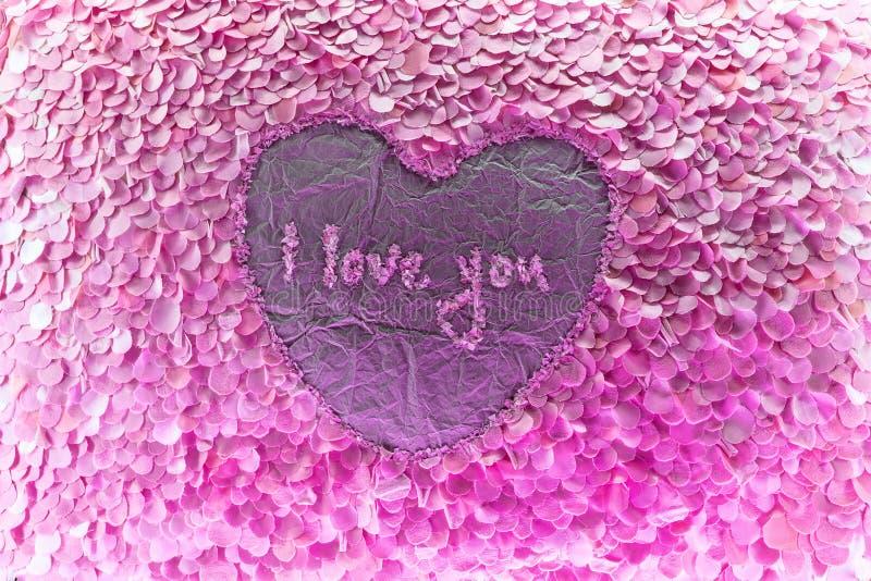 Corazón de papel con pétalos rosas fotos de archivo libres de regalías