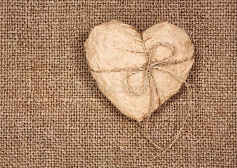 Corazón de papel en una arpillera fotos de archivo