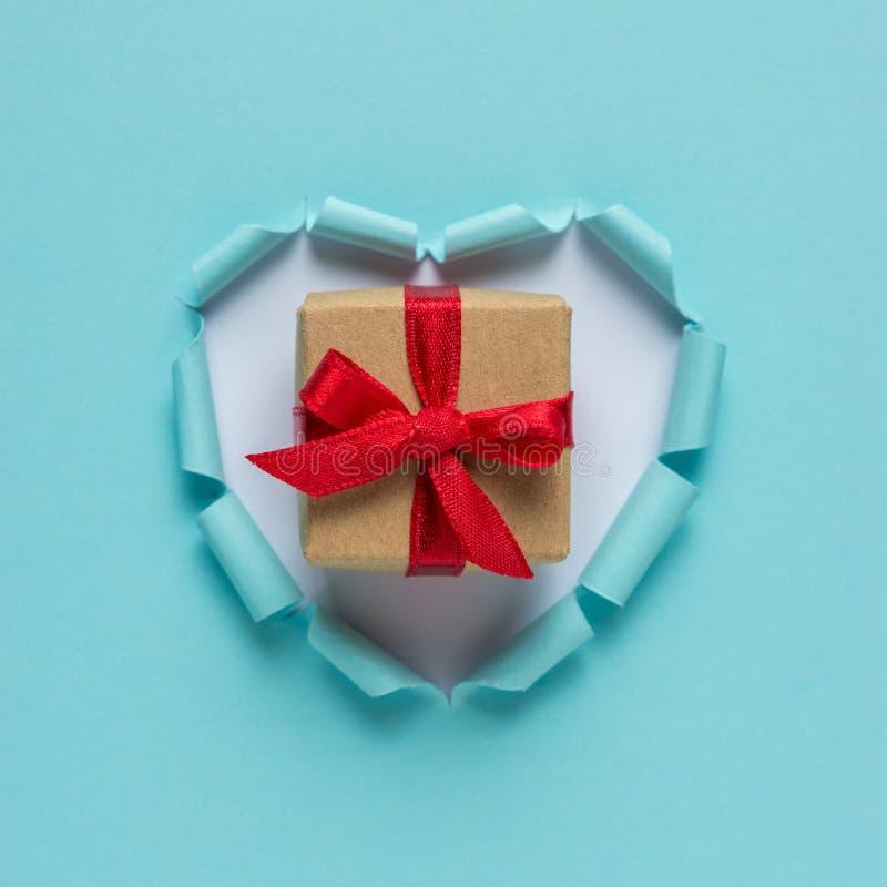 Corazón de papel rasgado vivo con la caja de regalo en fondo brillante imagen de archivo