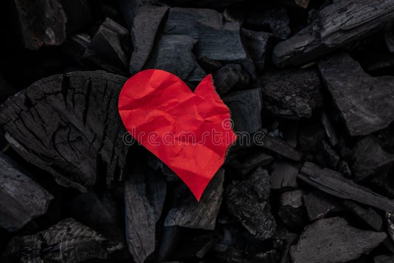 Corazón de papel rojo ardiendo en fondo mínimo de los carbones imagen de archivo libre de regalías