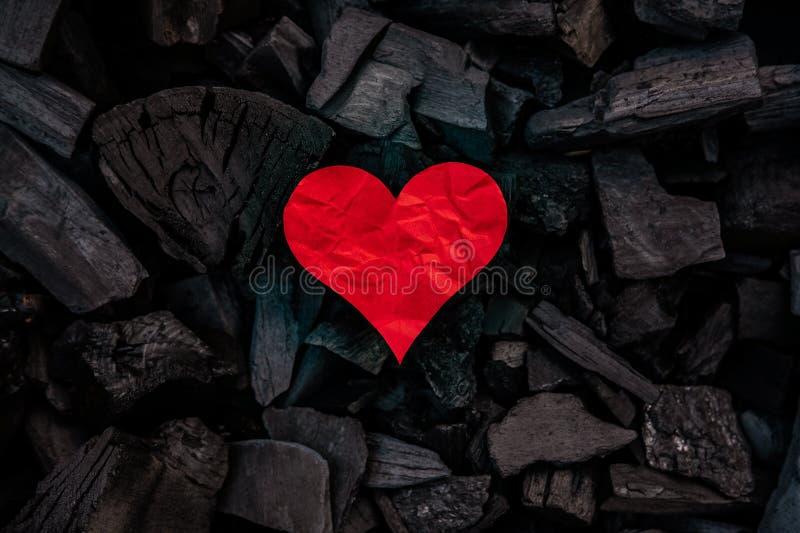 Corazón de papel rojo en fondo mínimo de los carbones imagenes de archivo