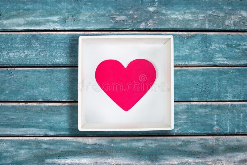 Corazón de papel rosado en la caja de cartón blanca en fondo de madera azul del vintage fotografía de archivo