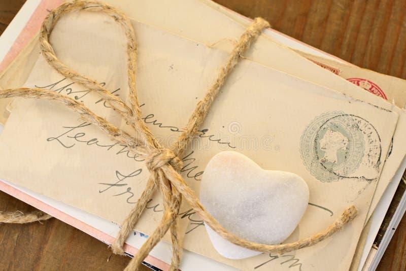 Corazón de piedra con las cartas atadas imágenes de archivo libres de regalías