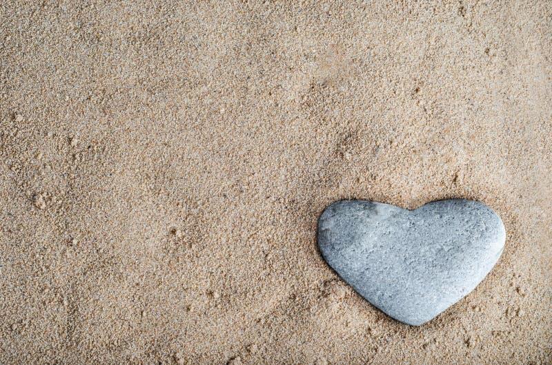 Corazón de piedra en arena fotografía de archivo