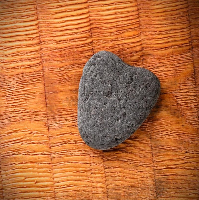 Corazón de piedra gris en el tablero de madera imagen de archivo libre de regalías