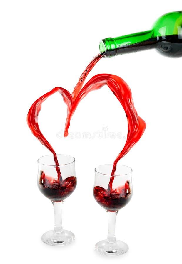 Corazón de verter el vino rojo fotografía de archivo