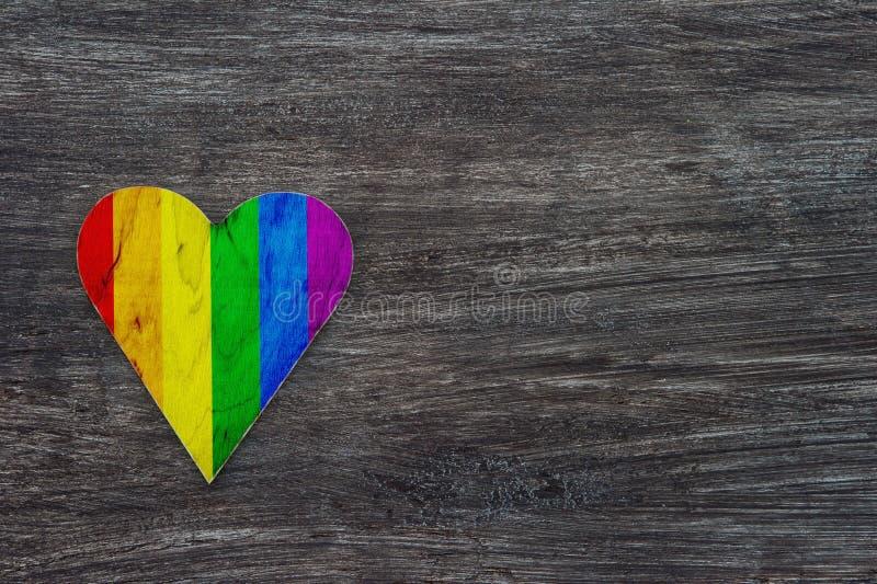 Corazón decorativo con las rayas del arco iris en Gray Wooden Background LGBT Pride Flag, símbolo de lesbiano, gay, bisexual, tra imagen de archivo