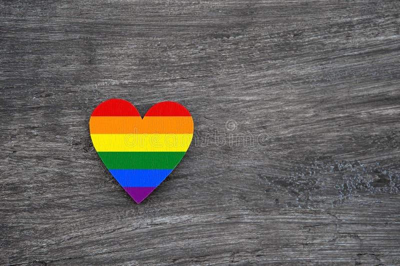 Corazón decorativo con las rayas del arco iris en Gray Wooden Background LGBT Pride Flag, símbolo de lesbiano, gay, bisexual, tra foto de archivo libre de regalías