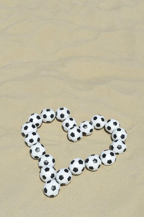Corazón del amor del fútbol hecho con los balones de fútbol en la playa fotos de archivo libres de regalías