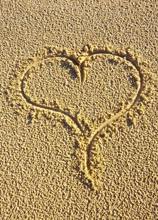 Corazón del amor dibujado en la arena imagenes de archivo