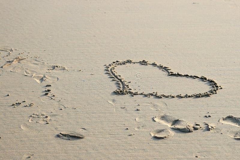 Corazón del amor drenado en la arena foto de archivo libre de regalías
