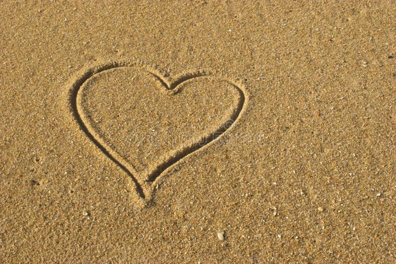 Corazón del amor en la arena fotografía de archivo