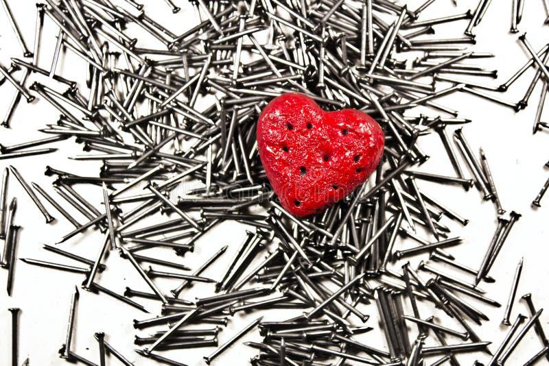 Corazón del amor en la pila de clavos del hierro fotografía de archivo libre de regalías