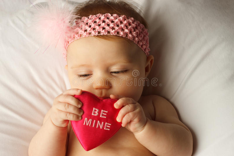 Corazón Del Asimiento Del Bebé De La Tarjeta Del Día De San Valentín Imagen de archivo