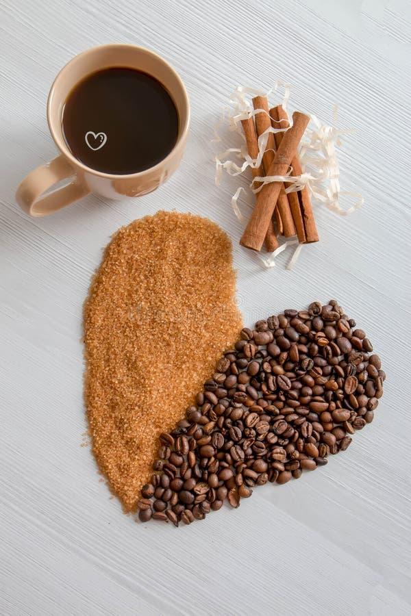 Corazón del café, con el azúcar marrón y el canela, y una taza de café imagen de archivo