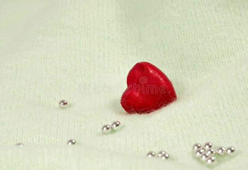 Corazón del chocolate en un abrigo rojo en un fondo ligero con las gotas brillantes imágenes de archivo libres de regalías