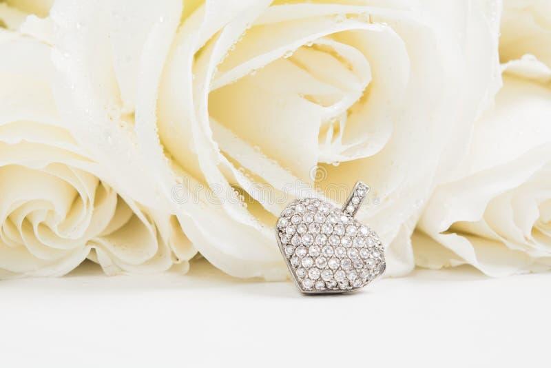 Corazón del colgante de oro de la joyería con los diamantes en fondo del ramo de las rosas blancas con el espacio de la copia Maq fotos de archivo