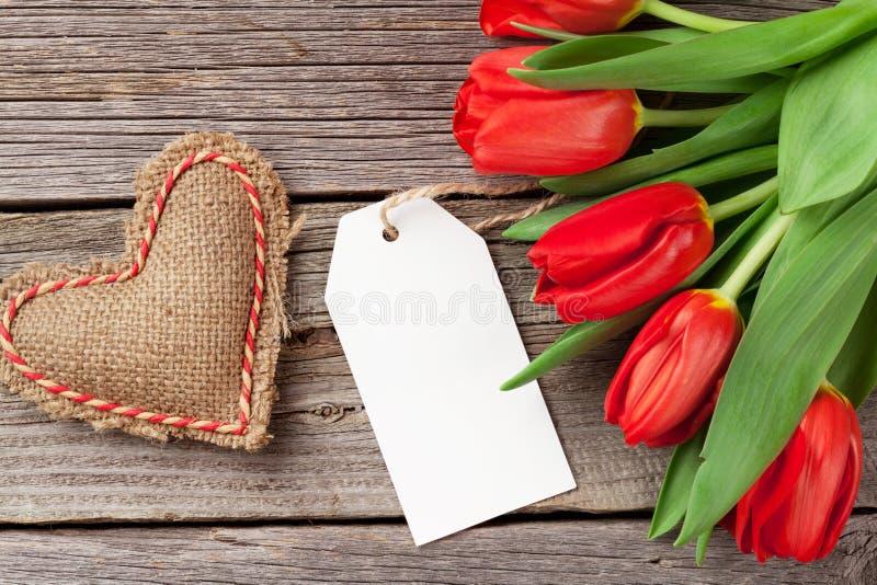 Corazón del día tulipanes y del ` rojos s de la tarjeta del día de San Valentín imagen de archivo libre de regalías