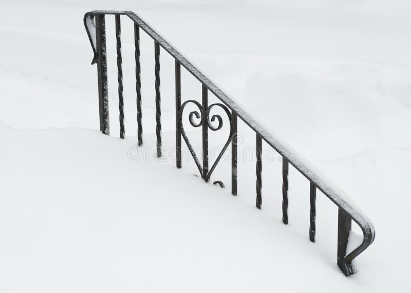 Corazón del hierro enterrado en nieve imágenes de archivo libres de regalías