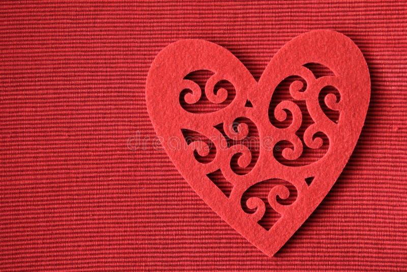 Corazón del recorte del fieltro del rojo en fondo rojo fotografía de archivo