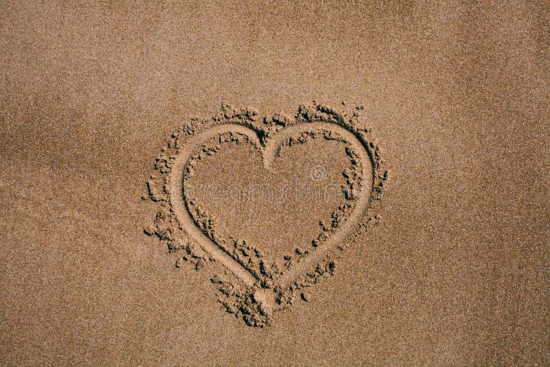 Corazón drenado en la arena Fondo de la playa con el dibujo del corazón Símbolo del amor de la forma del corazón como fondo foto de archivo libre de regalías