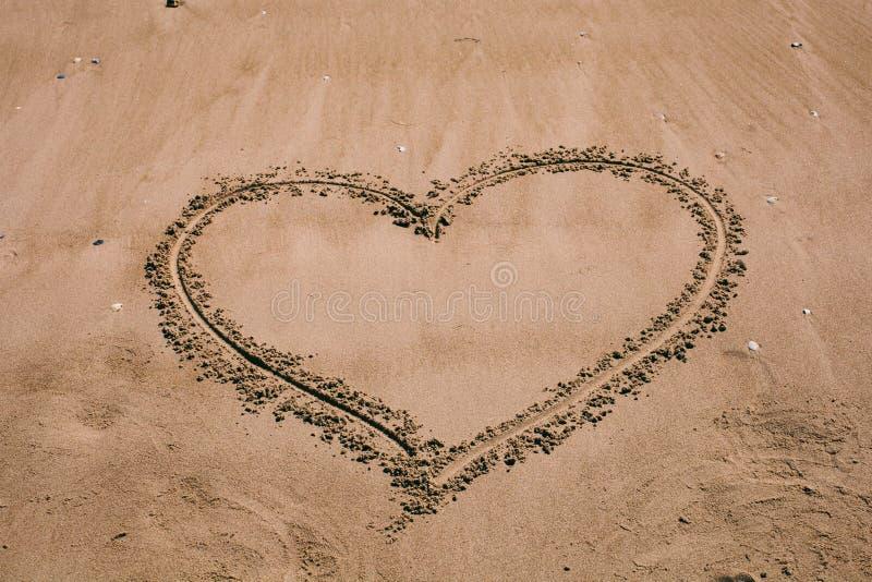 Corazón drenado en la arena Fondo de la playa con el dibujo del corazón Símbolo del amor de la forma del corazón como fondo imágenes de archivo libres de regalías