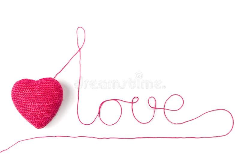 Corazón e hilado rojos en la forma de un amor de la palabra Aislado en el fondo blanco fotografía de archivo libre de regalías
