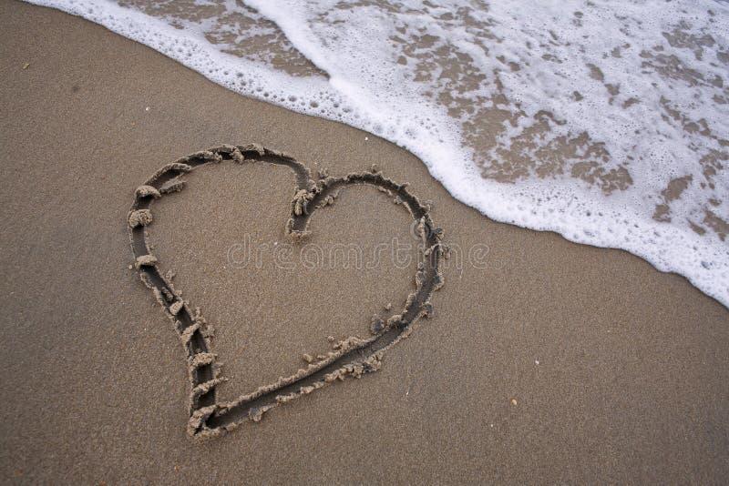 Corazón en arena - ame la playa imagen de archivo
