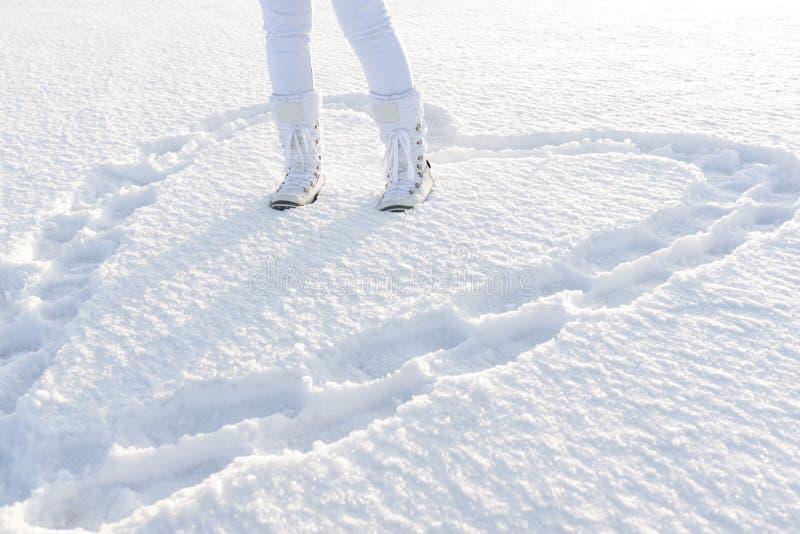 Corazón en nieve profunda por los pasos Concepto de amor Dre de las piernas de la mujer fotos de archivo