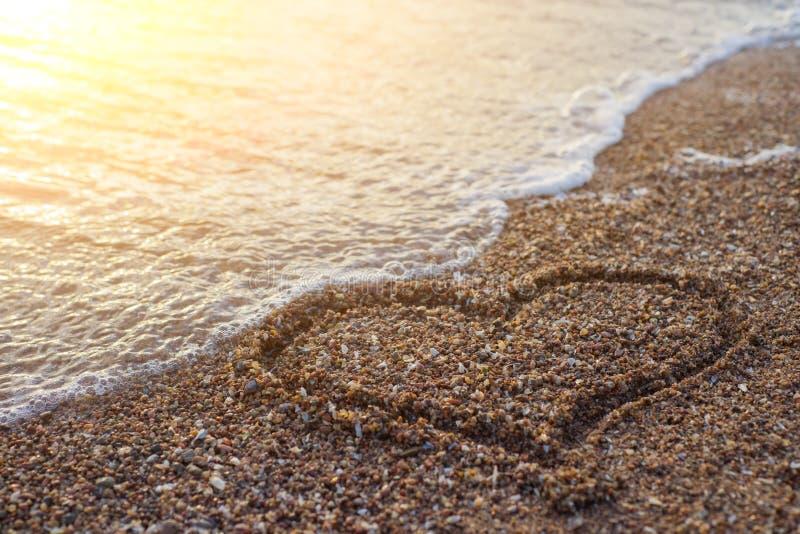 Corazón en una arena de la playa con la onda en fondo imagen de archivo libre de regalías
