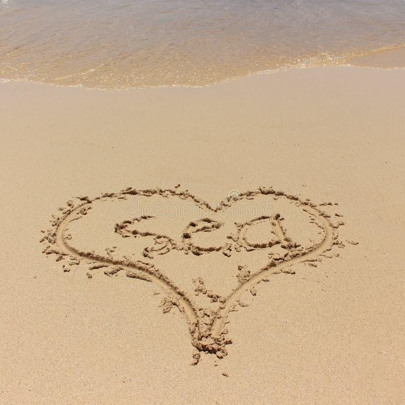 Corazón en una arena de la playa con la onda fotos de archivo