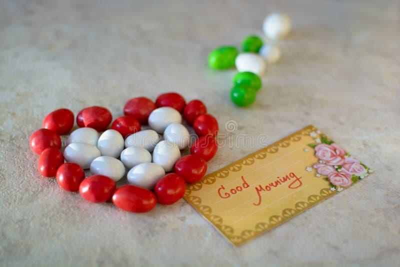 Corazón hecho de caramelos con el mensaje de la buena mañana imagenes de archivo