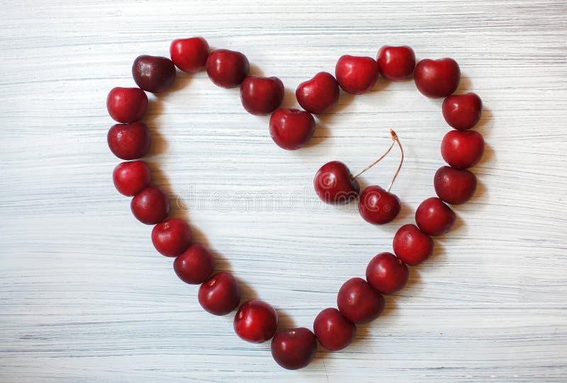 Corazón hecho de cerezas oscuras Fruta roja en fondo de madera El verano envía amor Partículas del arte fotografía de archivo