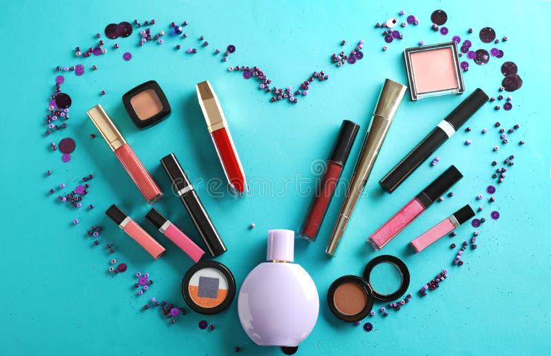 Corazón hecho de cosméticos decorativos en fondo del color fotos de archivo libres de regalías