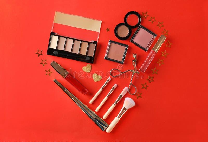Corazón hecho de cosméticos y de accesorios decorativos en fondo del color imágenes de archivo libres de regalías