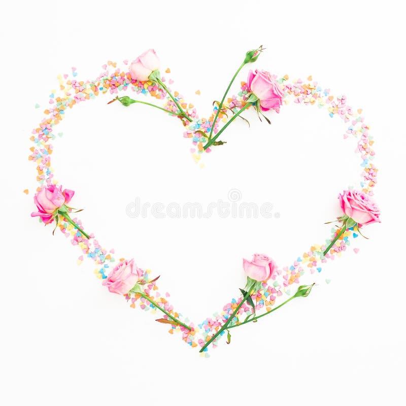 Corazón hecho de flores y de confeti rosados del caramelo en el fondo blanco Endecha plana, visión superior Composición del día d fotos de archivo