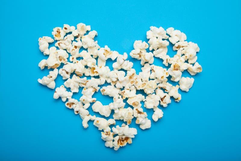 Corazón hecho de las palomitas deliciosas en un fondo azul imagen de archivo libre de regalías