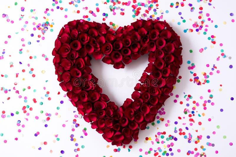 Corazón hecho de las rosas rojas adornadas con el confeti aislado en el fondo blanco foto de archivo
