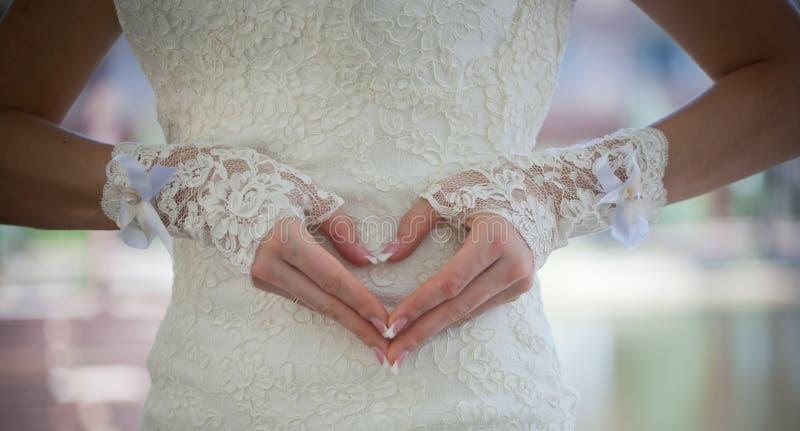 Corazón hecho de los dedos de las novias foto de archivo