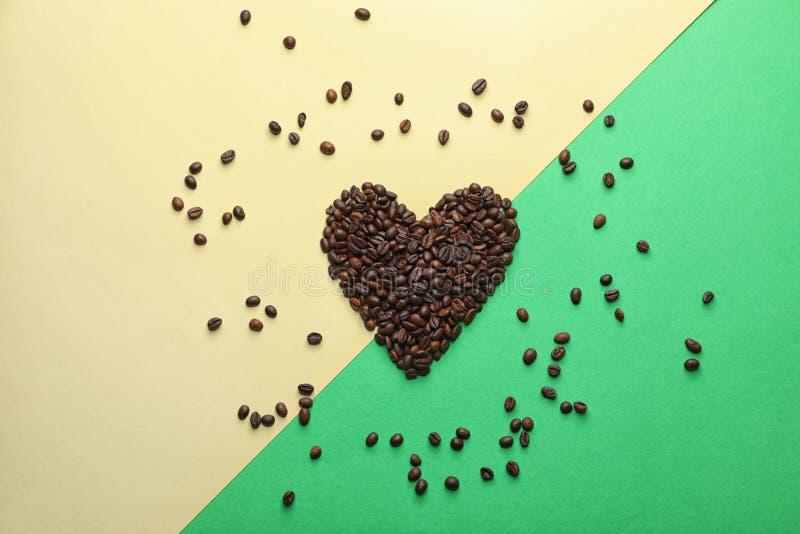 Corazón hecho de los granos de café en fondo del color imagen de archivo
