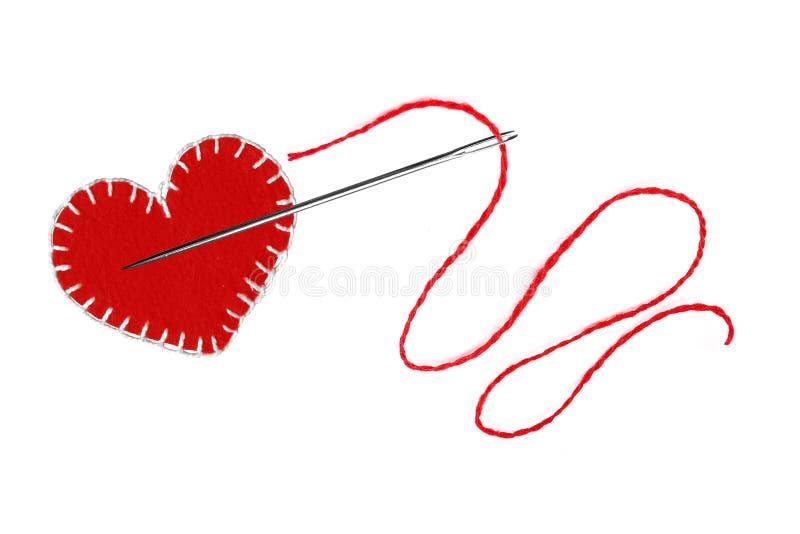 Corazón, hilo rojo y aguja aislados en blanco fotografía de archivo