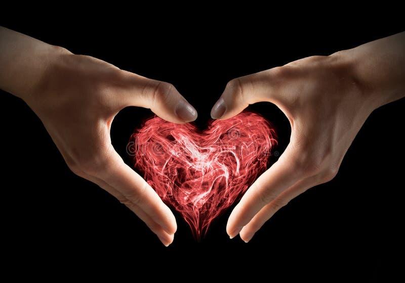 Corazón mágico en manos fotos de archivo